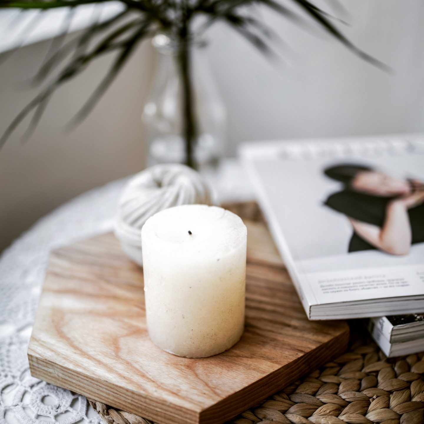 a cosy side table with a white candle which has had a small amount of burning on the wick next to a book