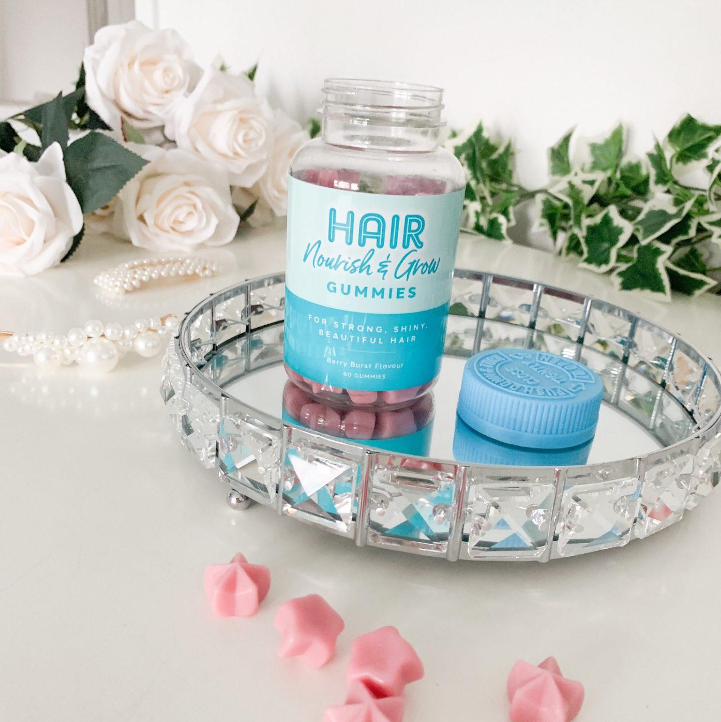 an open tub of Aldi hair nourish and glow gummies